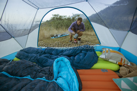 man brewing coffee outside pitched tent