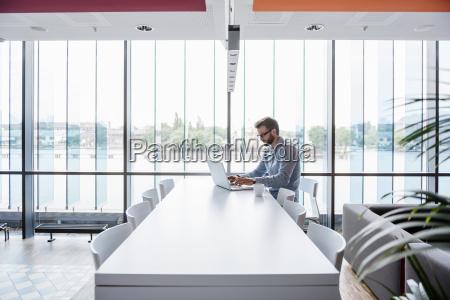 man using laptop sitting at conference