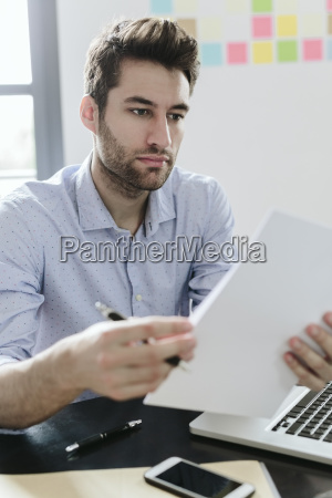 young businessman working in office reading
