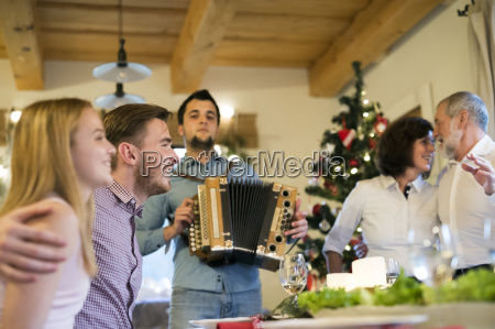 young man playing accordion for family