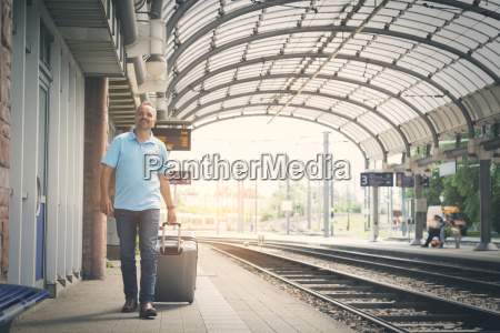 smiling man with luggage on platform