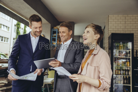 woman and two businessmen discussing plans