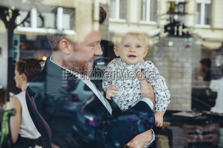 businessman holding his baby boy in