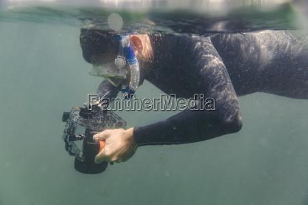 mann tauchen mit unterwasser dslr kamera
