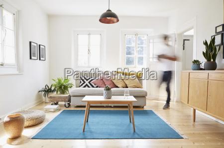 mann spaziert in hellem modernen wohnzimmer
