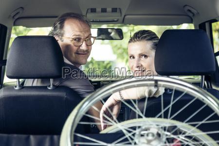 laechelnde paare im auto mit rollstuhl