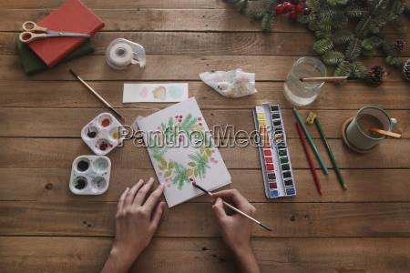 junge frau die weihnachtskarte mit wasserfarben