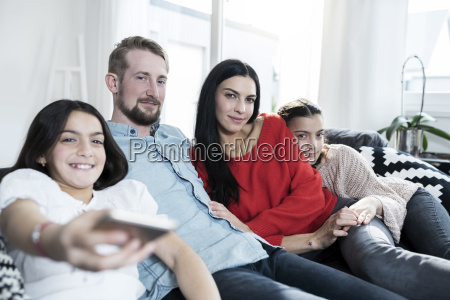 parents and twin daughters on sofa