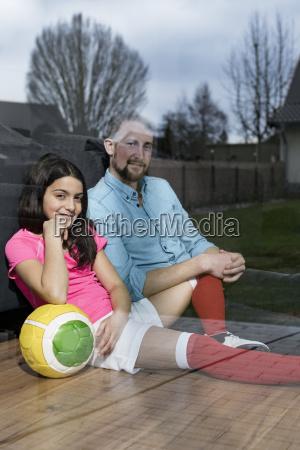maedchen im fussball outfit sitzt neben