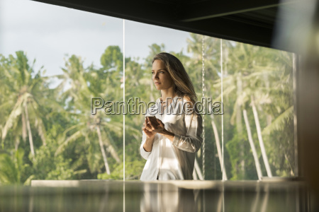 woman holding smartphone in design house
