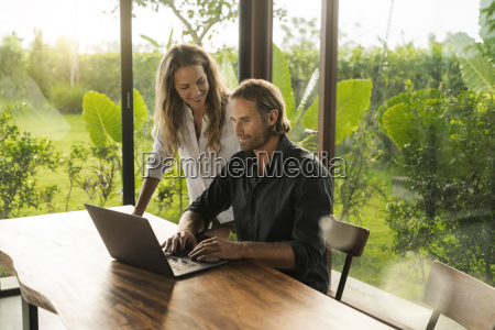 woman smiling at husband working on