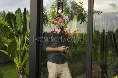 handsome man standing behind glass facade