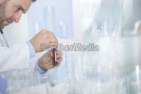 man examining test tube with liquid