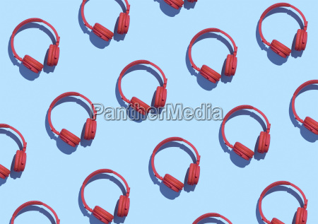 collection of red wireless headphones on