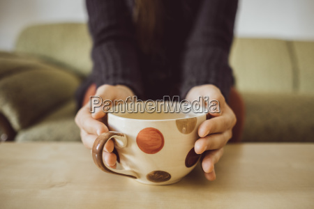 frau die haende halten teetasse nahaufnahme