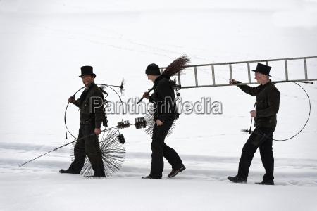 three chimney sweeps walking in snow