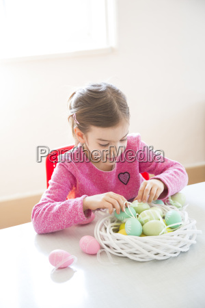 girl arranging coloured easter egg in