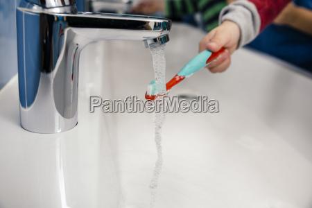 kind putzt seine zahnbuerste im badezimmer