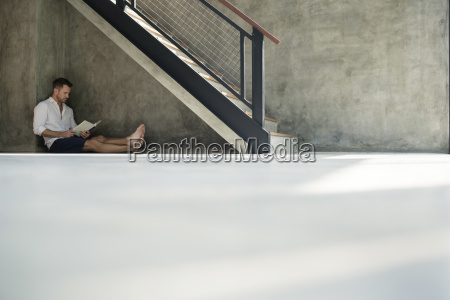 mature man sitting under staircase reading