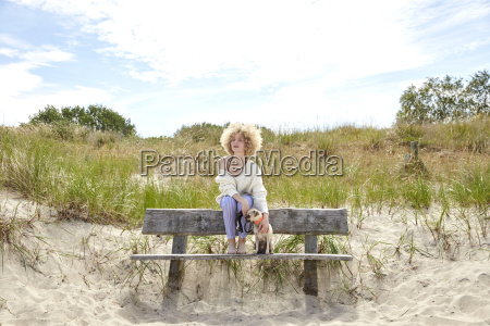 young woman sitting on bench in