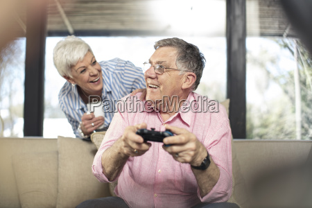 happy senior man with wife playing