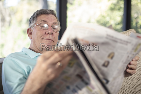 senior man sitting on couch reading