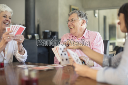 senior couple playing cards with daughter