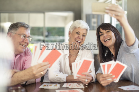 happy senior couple playing cards and