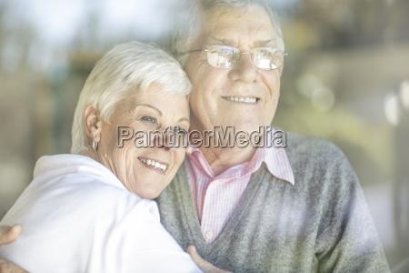 portrait of smiling senior couple behind