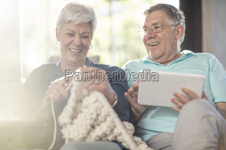 happy senior couple on couch at
