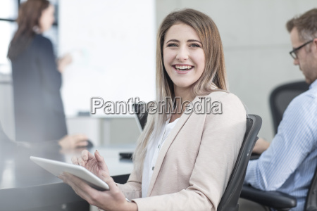 portrait of laughing businesswoman with tablet