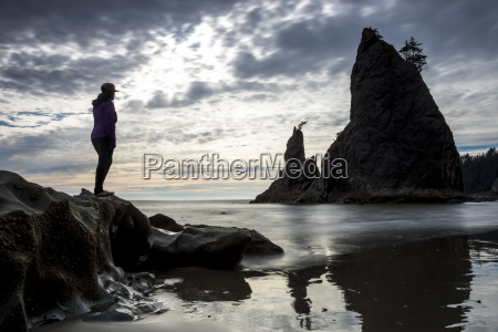 silhouette of woman standing on rock