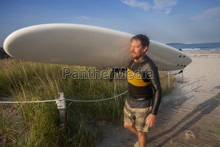 man carrying surfboard at nahant beach