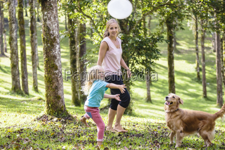 mother and daughter playing with dog