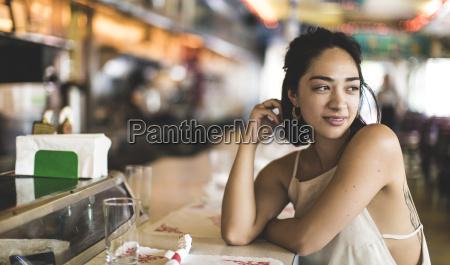 young woman sitting at a bar