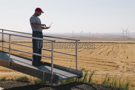 ein windparktechniker der einen laptop an