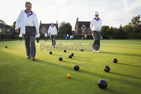 three lawn bowls players men walking