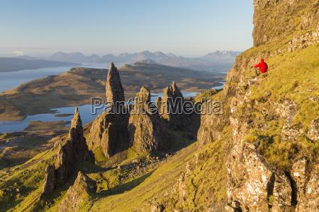 man sitting on slope admiring landscape