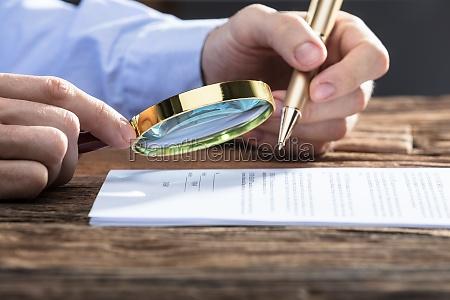 geschaeftsmann prueft dokument durch lupe