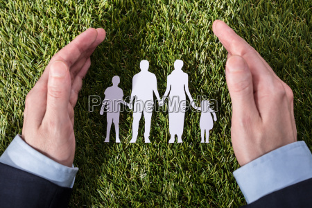 person protecting family paper cut out