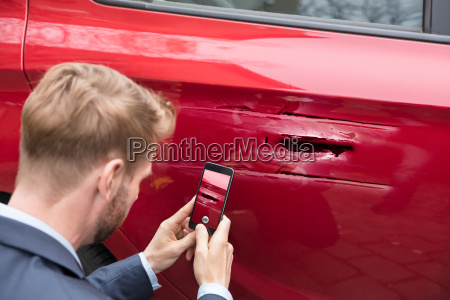 person taking picture of damaged car
