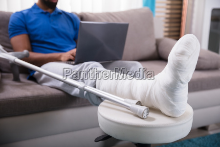 man with broken leg using laptop