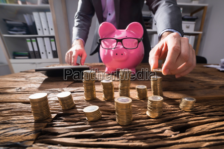 businessperson calculating stacked golden coins on