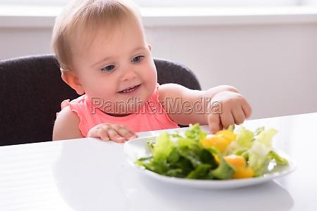 baby girl eating vegetable