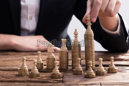 businessperson arranging chess piece on stacked