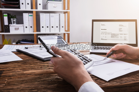businesspersons hand calculating bill with calculator