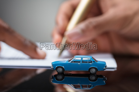 persons hand signing car loan agreement