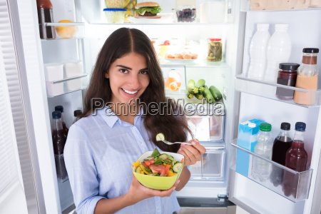 happy woman eating vegetable salad