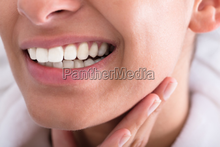 young woman holding toothache
