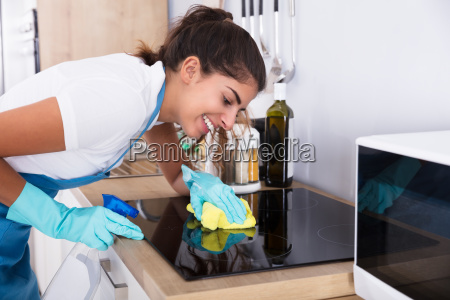 female janitor cleaning induction stove